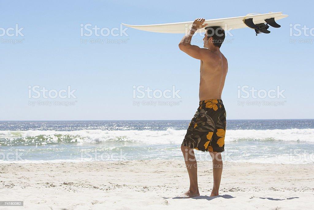 Homem com prancha de surf na praia foto de stock royalty-free