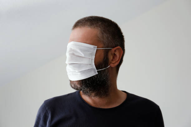 Man with surgical mask over the eyes stock photo