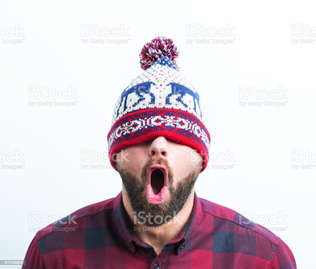 Man with surprised expression Portrait of surprised young man in winter cap on white background Adult Stock Photo
