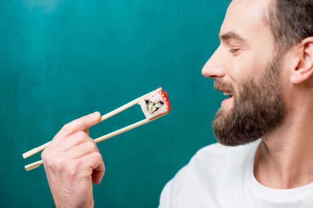 mann mit sushi - sushi essen stock-fotos und bilder