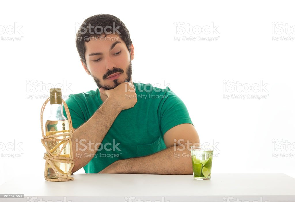 Man with suspicious look to cocktail drink. stock photo