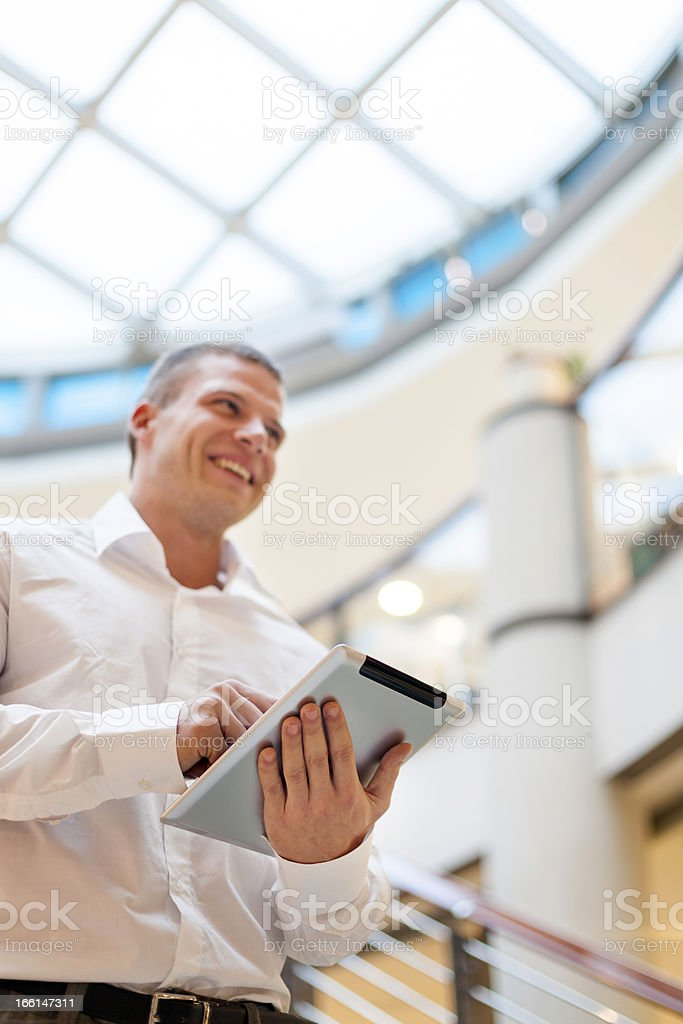 Man with tablet computer in modern business building royalty-free stock photo