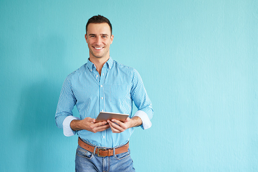 Smiling man with tablet computer standing in front of turquoise wall