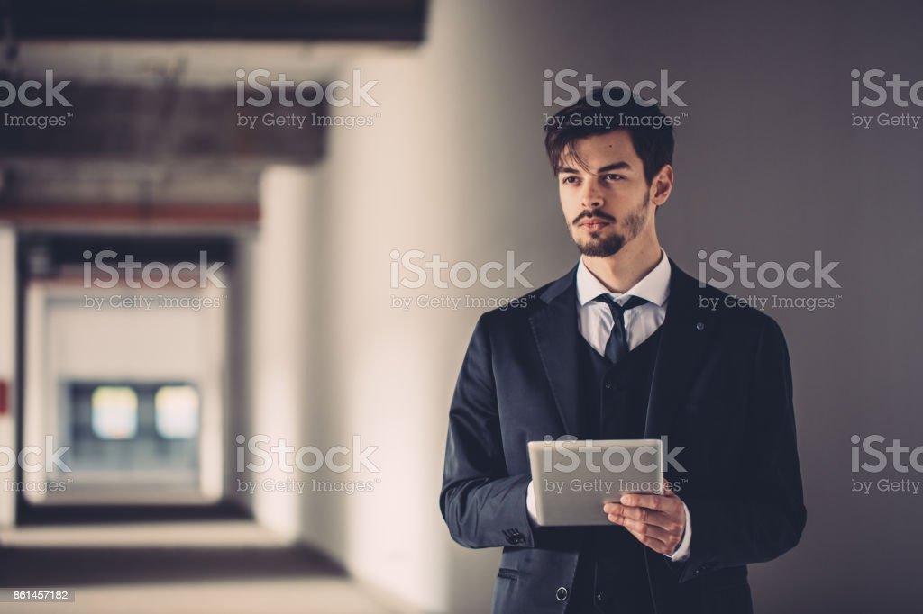 Man with tablet in stadium hallway stock photo