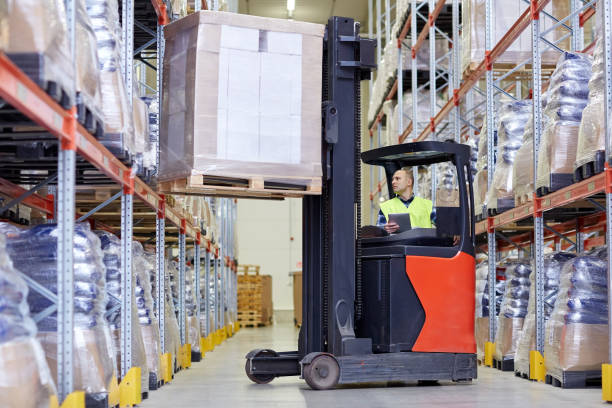 man with tablet pc operating forklift at warehouse stock photo
