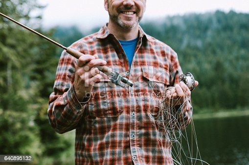 A humorous image of a man who has had his fly fishing equipment become extremely tangle up.  He smiles in spite of the frustrating situation.