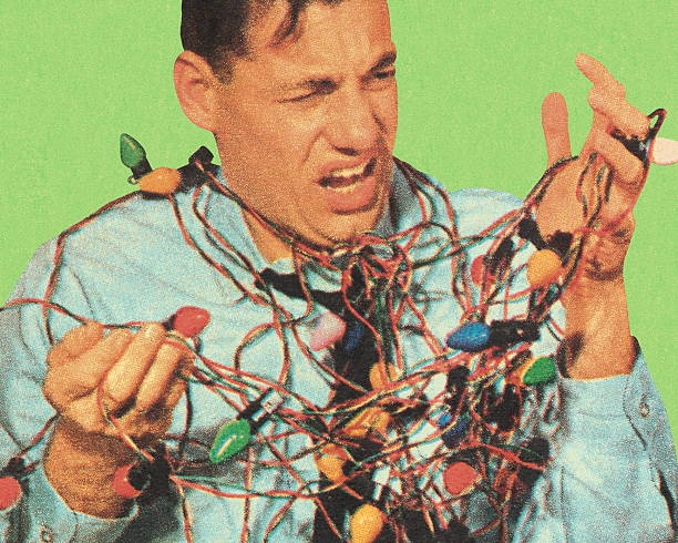 man with tangled christmas lights - tangled stock photos and pictures