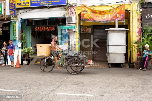 George Town, Penang Island Malaysia, December 26, 2018: Older man with tanned leathery skin rides a three wheeled cargo bike through the streets of George Town carrying garbage bags of cargo