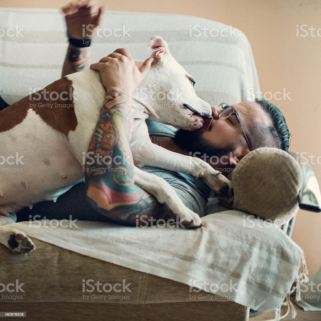 Man with tattoo embracing his dog. stock photo