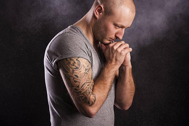 mann mit tattoo-druck - ruhegebet tattoo stock-fotos und bilder