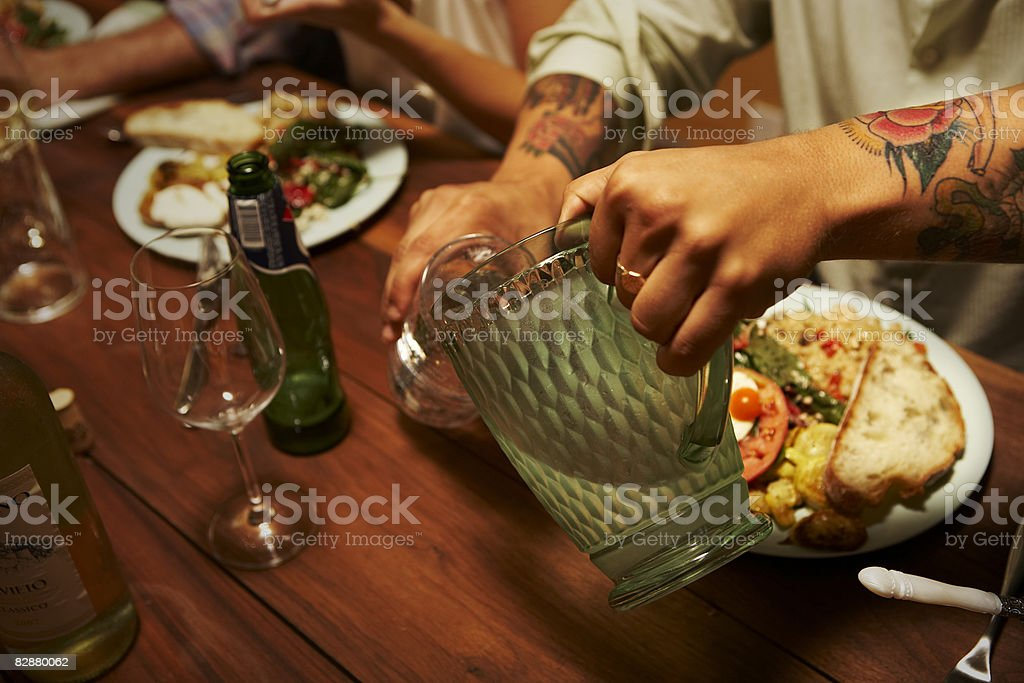Man with tattoo pouring glass of water  royalty free stockfoto