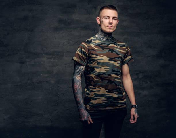 ein mann mit tattoos auf hals, gesicht und armen, gekleidet in einer camouflage-t-shirt. - gesichtstattoos stock-fotos und bilder