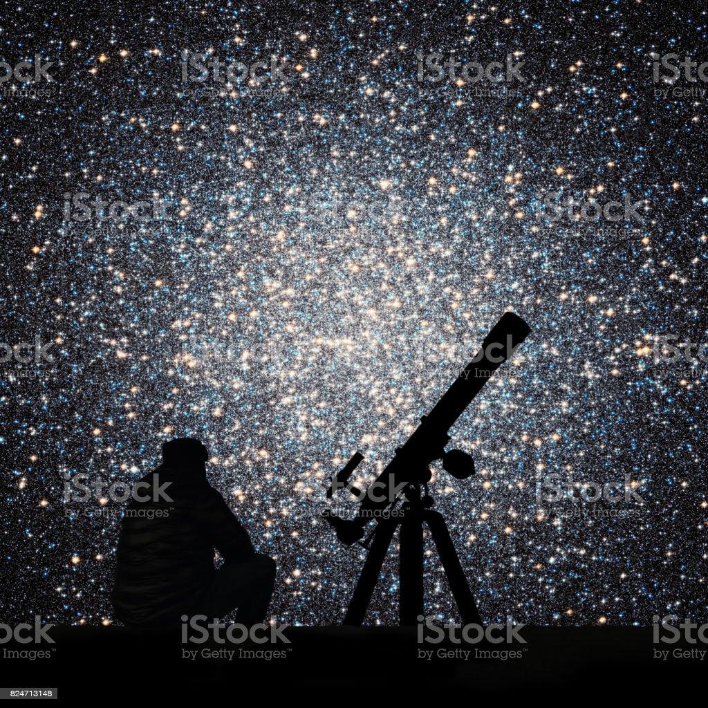 Man with telescope looking at the stars. Globular cluster Omega Centauri in constellation Centaurus stock photo