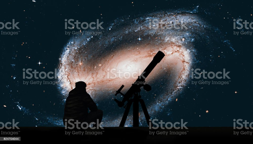 Man with telescope looking at the stars. Spiral galaxy in the constellation Eridanus NGC 1300 stock photo