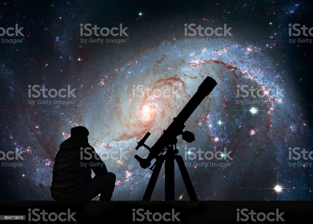 Man with telescope looking at the stars. Stellar Nursery NGC 1672. Spiral galaxy in the constellation Dorado stock photo