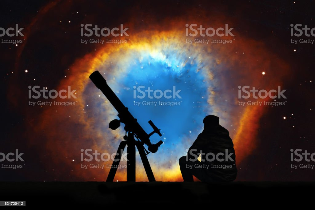 Man with telescope looking at the stars. The Helix Nebula or NGC 7293 in the constellation Aquarius. stock photo