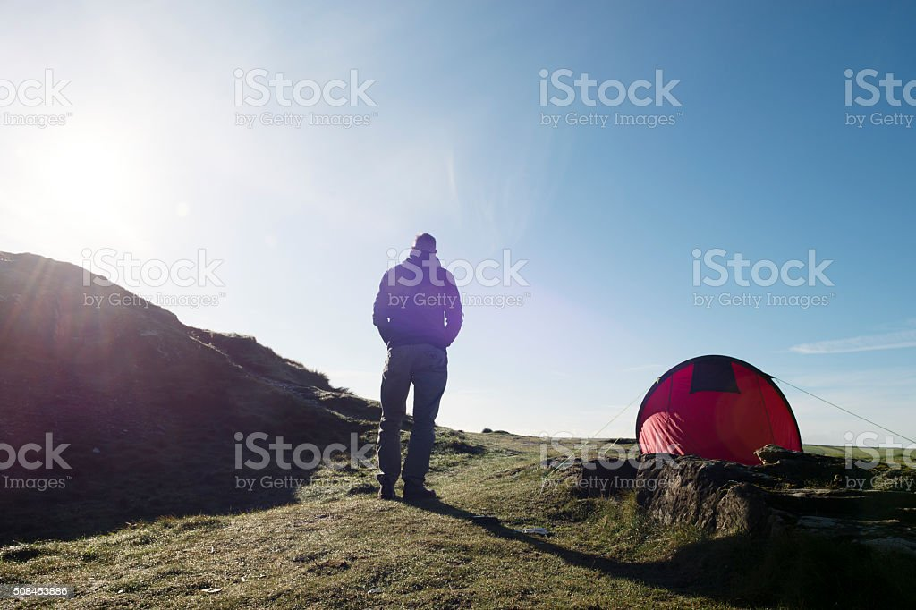 Man with Tent in sun flare on the Cornish Coast. stock photo
