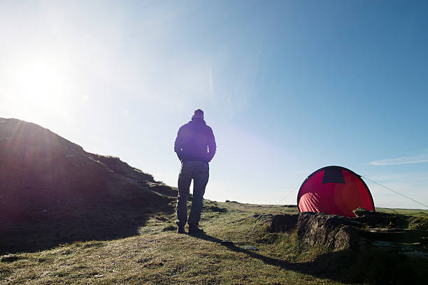 man with tent in sun flare on the cornish coast. - tent stock photos and pictures