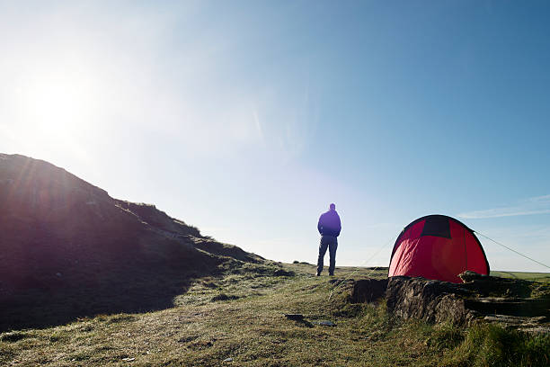 man with tent in sun flare on the cornish coast. - tent stock pictures, royalty-free photos & images