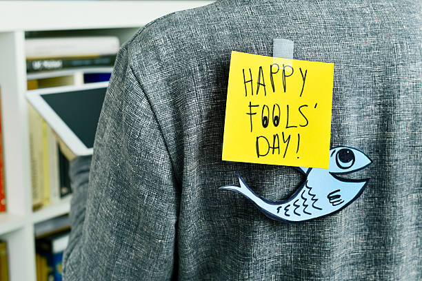 man with text happy fools day attached to his back closeup of a young man with a paper fish and a note with the text happy fools day attached with tape to his back april fools day stock pictures, royalty-free photos & images