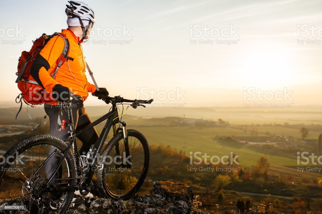 Man with the bike standing on a rock. spring nature stock photo