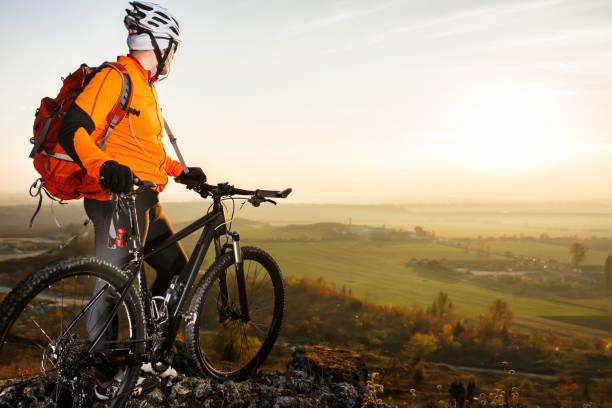自転車を持った男が岩の上に立ってる春の自然 - 自然旅行 ストックフォトと画像