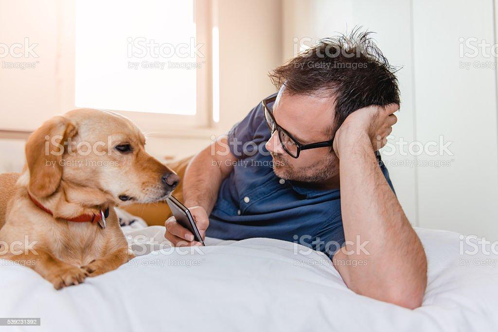 Homem com o cão com telefone inteligente na cama foto royalty-free