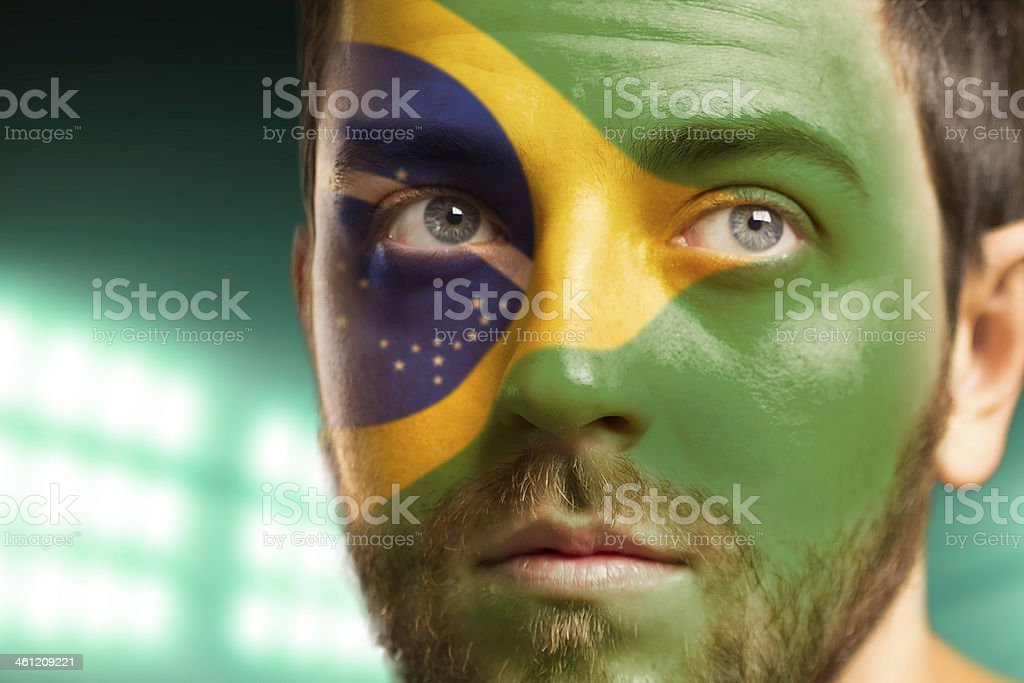 Man with the flag of Brazil painted on his face stock photo