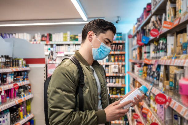 L'homme avec le masque sur son visage au supermarché est à la recherche d'un désinfectant - Photo
