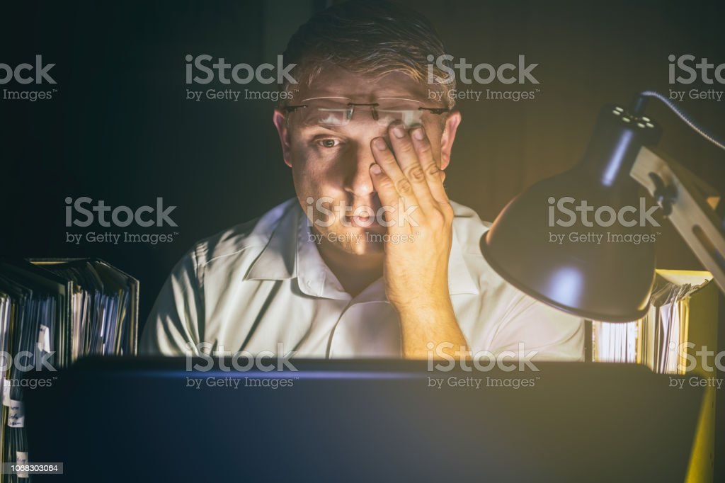 Man with tired eyes due to too much work on the computer screen working late Adult Stock Photo