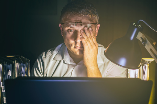 Man With Tired Eyes Due To Too Much Work On The Computer Screen Stock Photo - Download Image Now
