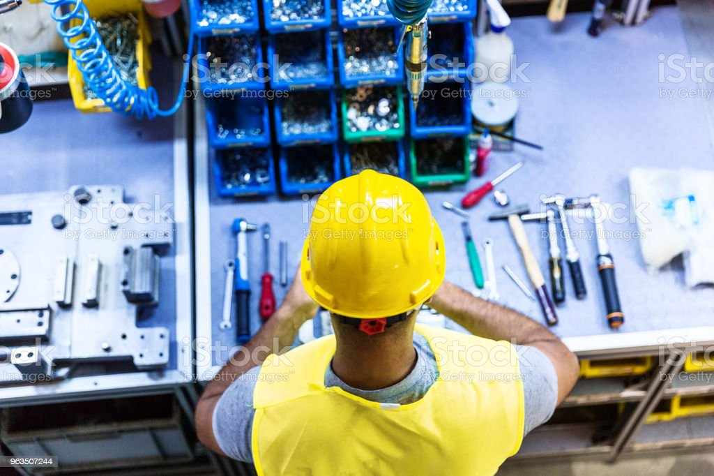 Man with Tools on Industrial Workbench stock photo