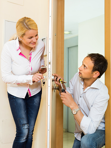 Man with tools repairing door lock for young blonde housewife