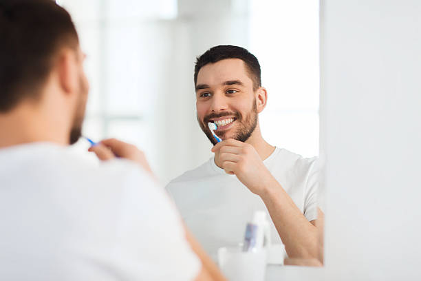 man with toothbrush cleaning teeth at bathroom stock photo