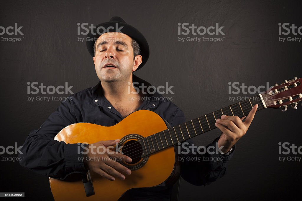 Man with top hat playing guitar royalty-free stock photo