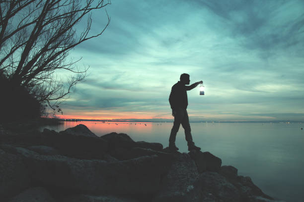 Man with torch walking on rocks at lake in night Man with torch walking on rocks at lake in night flaming torch stock pictures, royalty-free photos & images