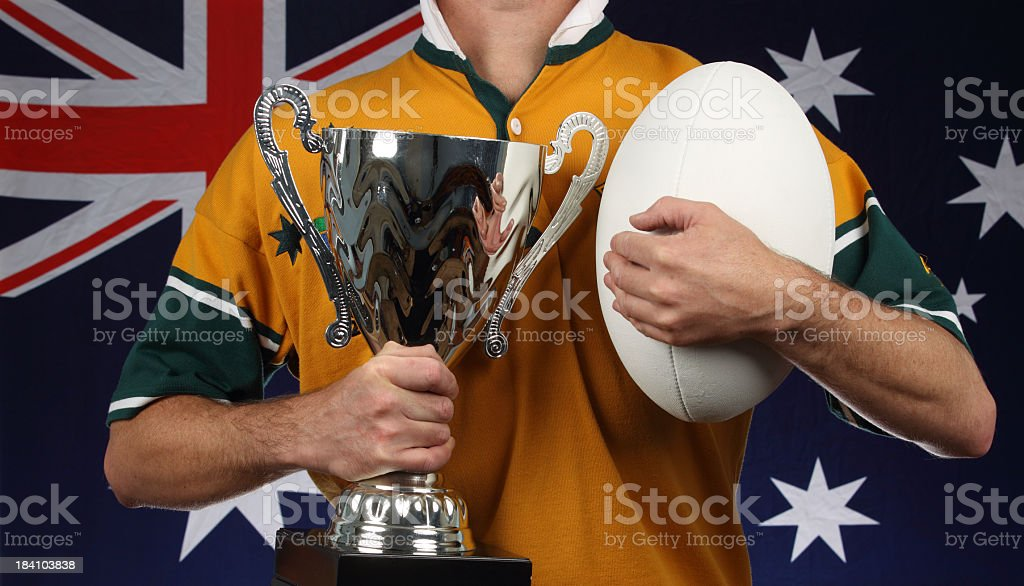 Man with trophy and rugby ball in front of Australian flag royalty-free stock photo