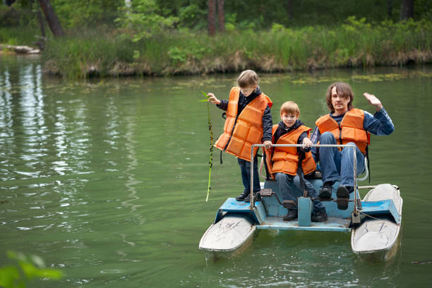 Hombre con dos hijos está nadando en un catamarán de pedal - foto de stock