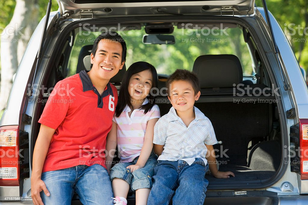 Man with two children sitting in back of van smiling royalty-free stock photo