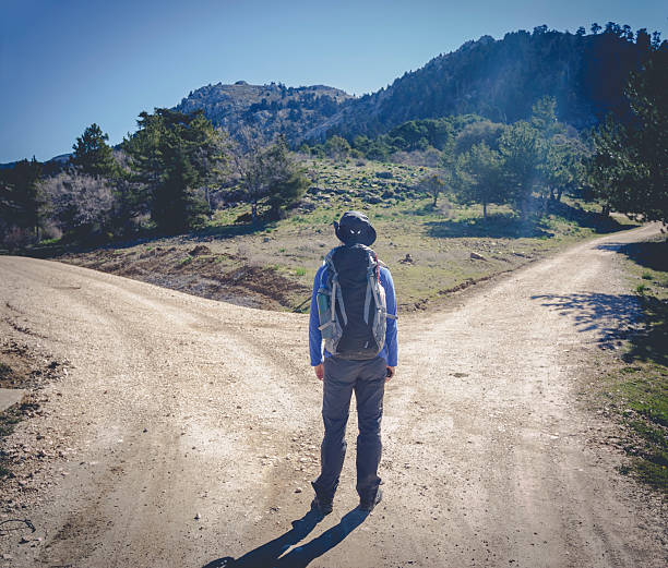 Man with two different ways Hiker man choose between to directions at the mountain fork in the road stock pictures, royalty-free photos & images