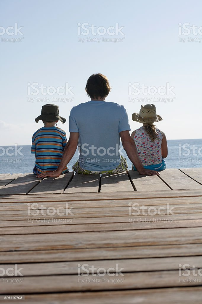 Man With Two Kids Sitting On Jetty stock photo