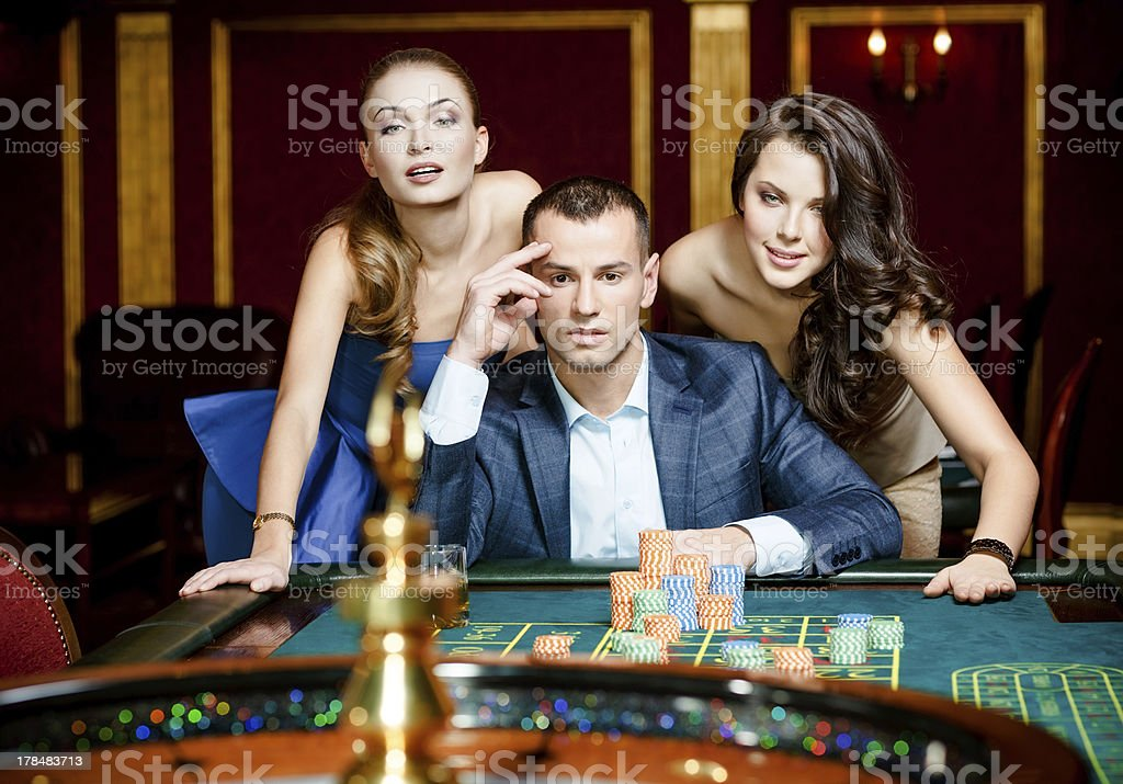 Man with two ladies playing roulette at the casino royalty-free stock photo