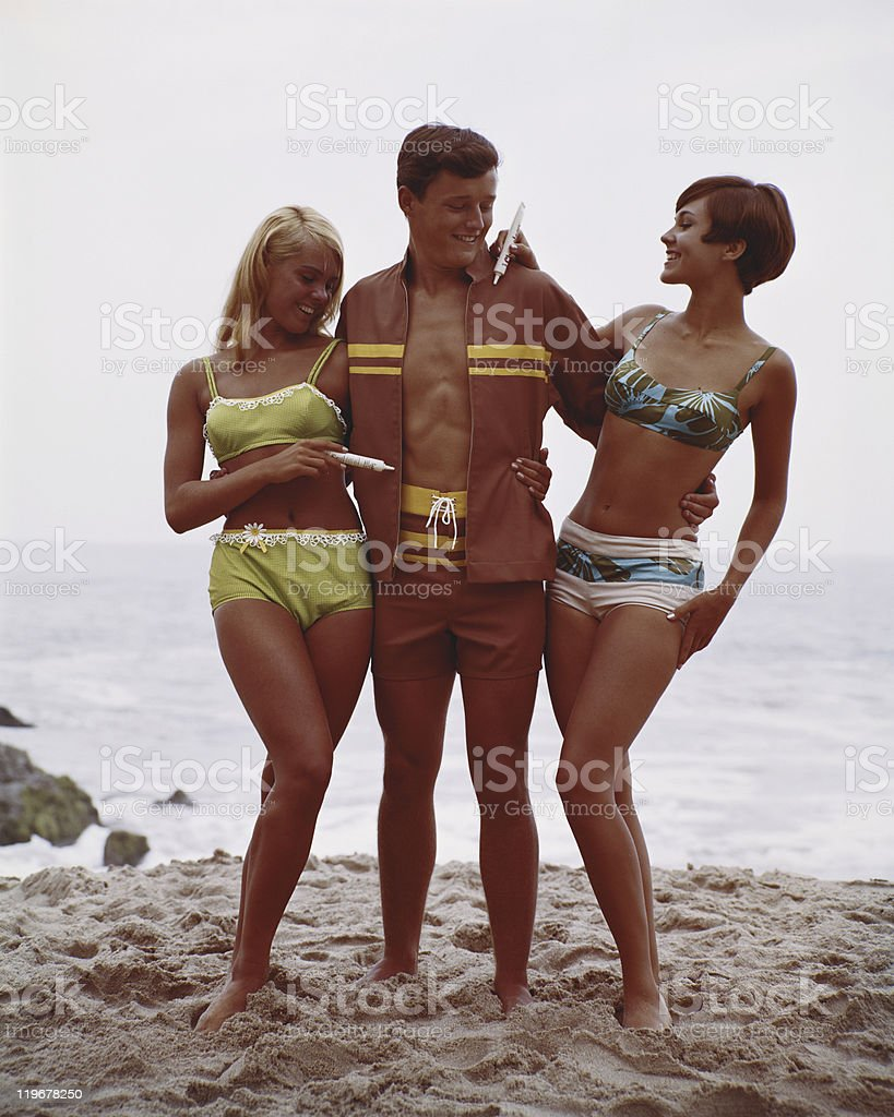 Man with two women standing on beach, smiling stock photo