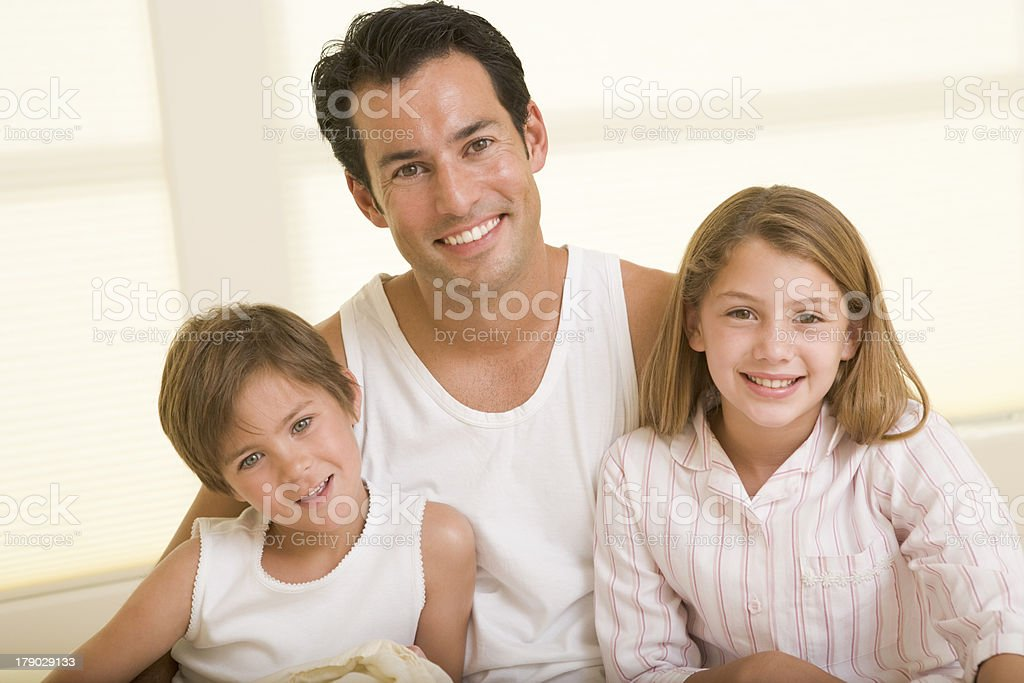 Man with two young children sitting in bed smiling royalty-free stock photo