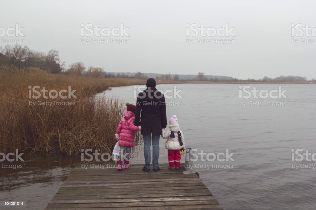 A man with two young girls at the river pier. stock photo