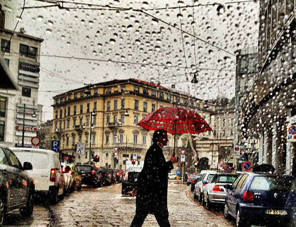 Man with umbrella crossing street under rain in Milan, Italy stock photo