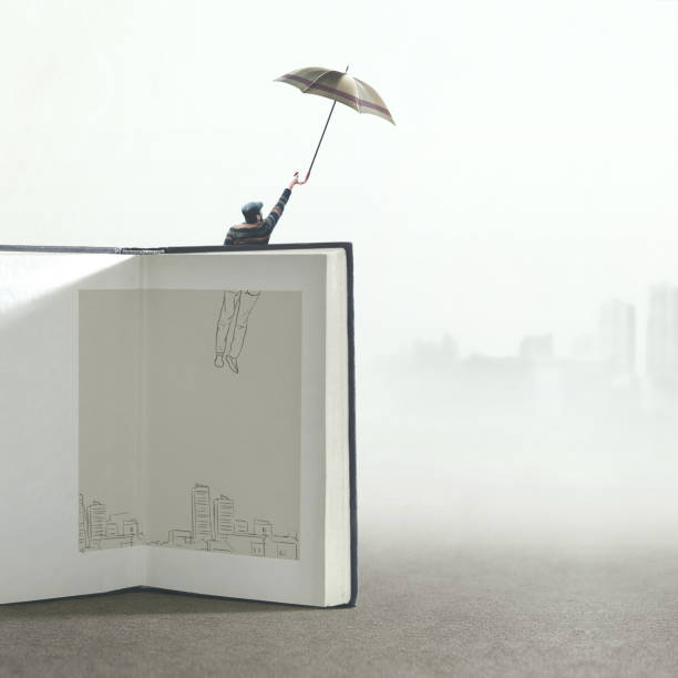 man with umbrella flying out of a illustrated book; surreal concept stock photo