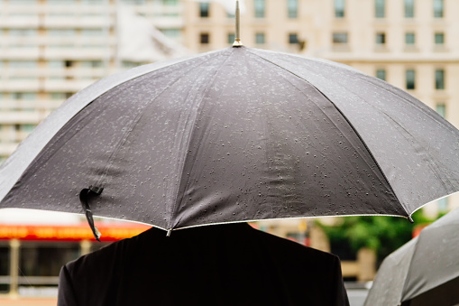Man with umbrella on the street seen from behind