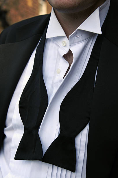 Man with untied black bowtie and unbuttoned white shirt stock photo