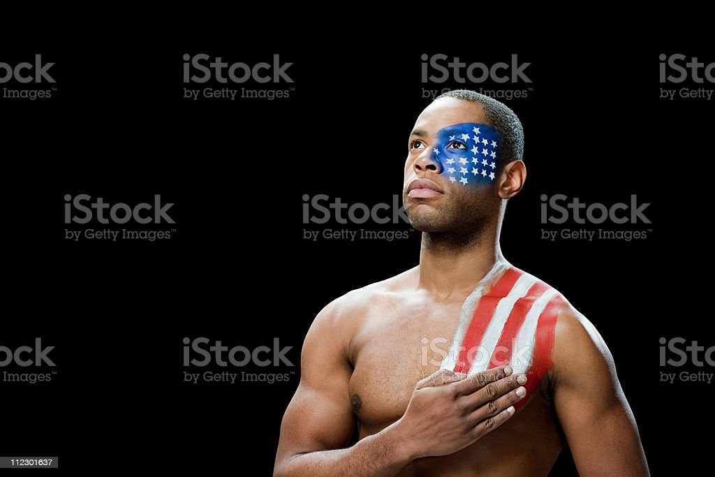 Man with US flag painted on face and shoulder, hand on chest royalty-free stock photo